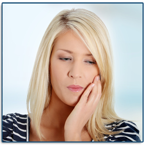 A blonde woman hodling her left cheek and jaw in pain