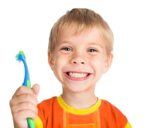 Boy smiling and holding a toothbrush