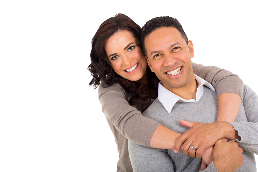 Couple in neutral color sweaters smiling on white background.