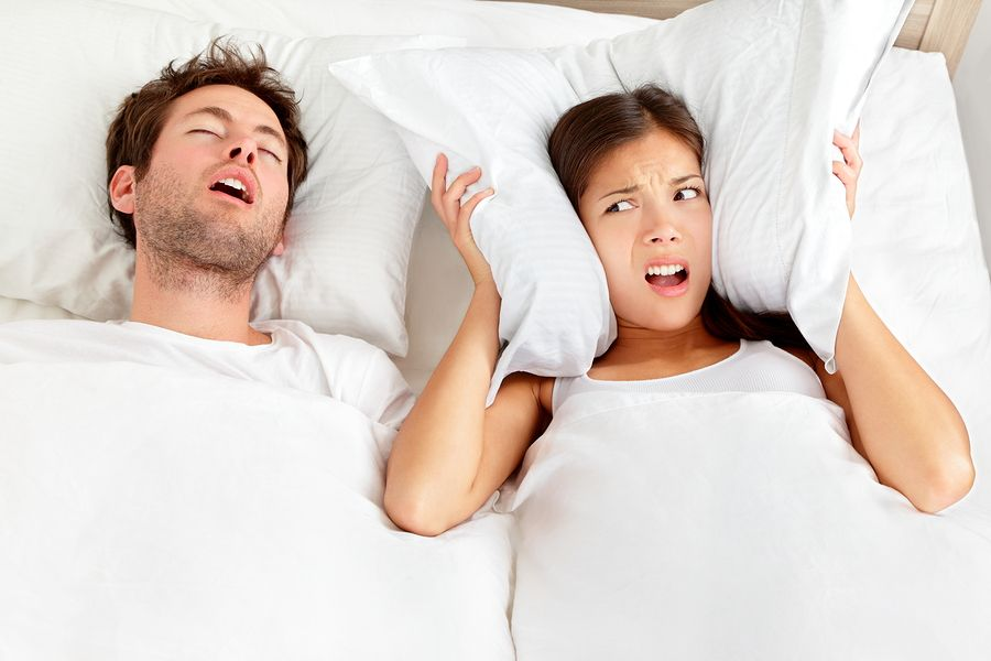 Couple in bed, man snoring and woman can not sleep, covering ears with pillow for snore noise.