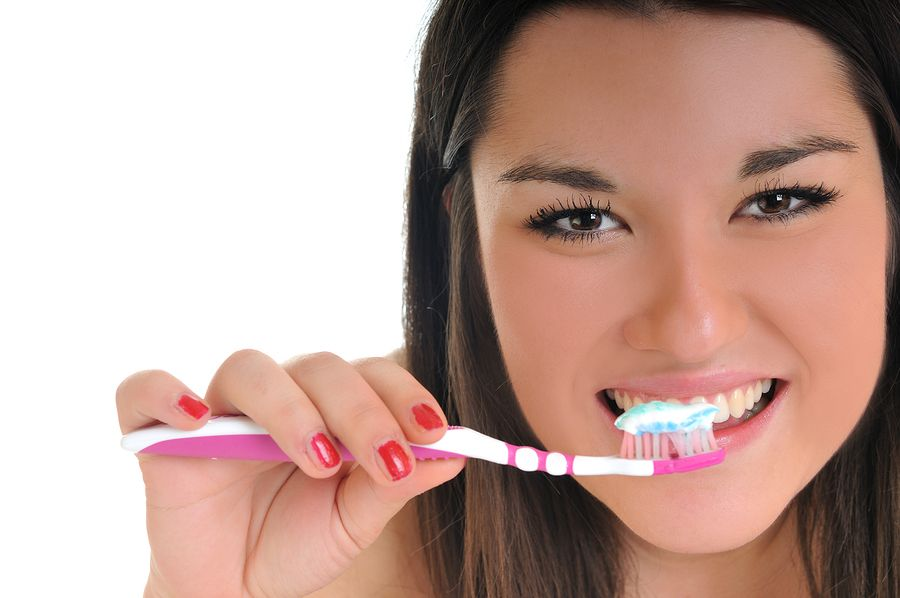 Smiling young woman holding tooth brush