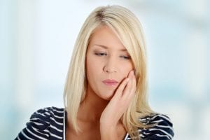 Young woman in pain is having toothache.