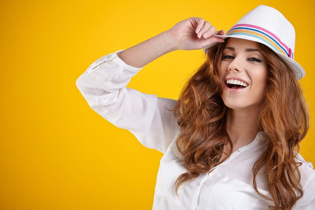 woman with hat in a yellow background