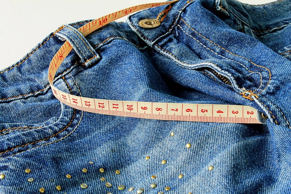 Measuring tape on pair of jeans